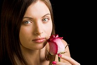 Young charming woman holding fresh pink rose by her face and looking at camera with serene expression