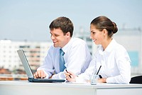 Portrait of businesswoman and businessman looking at monitor of laptop outdoor