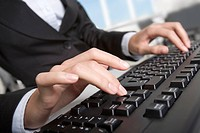 Close_up of secretary typing business document on the black keyboard