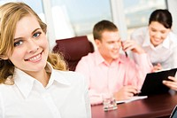 Portrait of blonde woman looking at camera in working environment in office