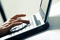 Close_up of businesswomans fingers pushing keys of laptop on desk