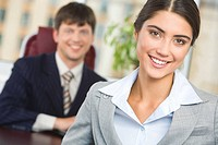 Portrait of happy businesswoman looking at camera on background of confident man