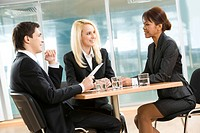 Photo of successful employees gathered around table explaining their ideas in office