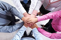 Close_up of business people standing and keeping hands on top of each other