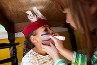 Girl putting Native American face paint on another girl