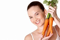 Portrait of pretty girl with ripe carrots smiling at camera over white background