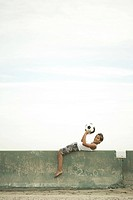 Boy lying on wall with football
