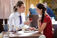Image of elegant man making proposal to beautiful woman in restaurant during romantic dinner