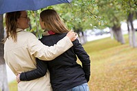 Rear view of affectionate couple walking under umbrella