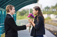 Photo of happy girl with aster bouquet smiling to handsome guy outside