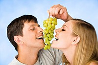 Portrait of man and young woman eating bunch of grapes