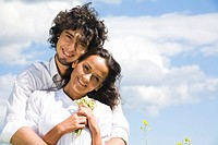 Portrait of smiling couple in white shirts on the background of sky