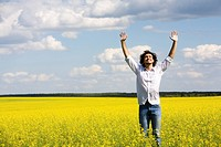 View of smiling man raising his hands standing in the field