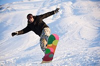 Image of brave man practicing snowboarding in winter