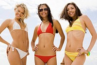 Portrait of three slim girls in bikini smiling at camera on the beach