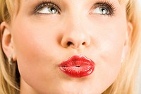 Close_up of pretty blonde looking aside with her lips fixed in kiss