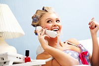 Portrait of female in curlers speaking on the telephone at home