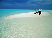 Businessman with laptop in chair on isolated sandbar                                                                                                  ...