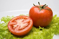 Close_up of foods: tomatoes placed on the green leaves