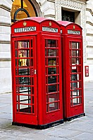 Two red telephone boxes near on London sidewalk