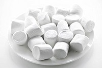 Close up of many plump sweet marshmallows on plate