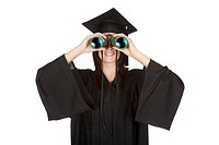 Beautiful Caucasian woman wearing in a black graduation gown and looking through binoculars