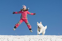 Girl jump in snow with dog