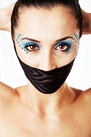 Beautiful female fashion face with blue makeup and gems rhinestones of a Caucasian Hispanic woman with hands behind head and bare shoulders and mouth ...