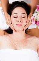 Skincare consultant applying fasial massage on beautiful woman at a spa salon