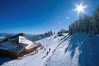 Skiers outside Midway Lodge at Red Lodge mountain resort ski area in Montana, USA