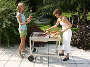 Two women ar barbecuing_grilling meat on a terace