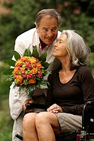 Older man gives flowers to his wife