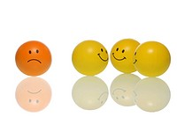 A frowning smiley, frownie standing apart from a group of smileys, symbolic image for bullying