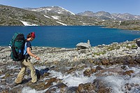 Young woman crossing a creek, hiking, backpacking, hiker with backpack, historic Chilkoot Pass, Chilkoot Trail, Crater Lake behind, alpine tundra, Yuk...