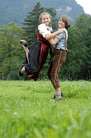 Girl and Boy in traditional Costumes playing in a Meadow, Bavaria