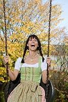 Woman wearing a Dirndl on a Swing