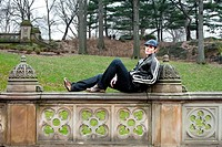 Handsome caucasian guy sitting on railing with landscape background