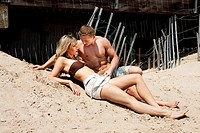 Beautiful sexy fashion couple, guy and girl, wearing bathing clothes while at the beach  both laying romantically on the sand in front of the boardwal...