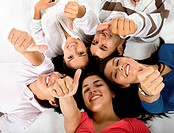 Happy group of friends lying on the floor with thumbs up isolated on white