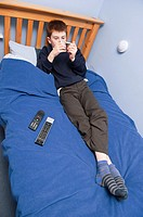 A picture of an eleven year old boy playing with his ipod touch in his bedroom in the Uk