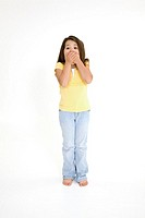 Five year old female child standing on white background with a surprised look wearing casual clothes