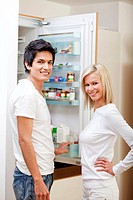 Couple at home looking inside the fridge and smiling