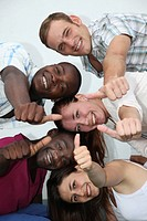 young, happy people from different backgrounds have fun and show their thumb in the direction of camera