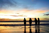 Silhouette shots of four girls on the beach enjoying the dramatic sunset