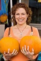 Woman holding two pumpkins at farmers´ market, Nevada City, California
