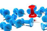 A red push pin among blue push pins concept of winning