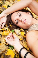 A portrait of a beautiful caucasian woman lying down on autumn leaves on the ground