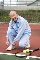 A shot of a senior asian tennis player tying up his shoes