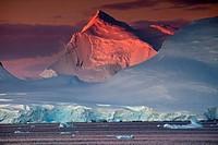 Alpenglow lights up high peaks on Wiencke and Anvers Islands behind Port Lockroy, Antarctic Peninsula.