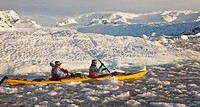 Kayakers paddle in brash ice among icebergs, Cierva Cove, Antarctic Peninsula.